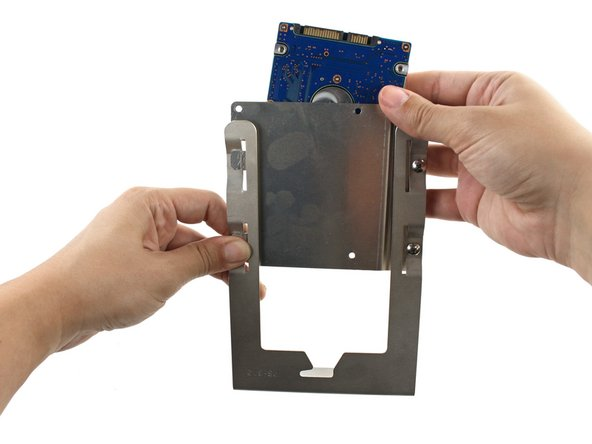 Align the holes in the hard drive with the three holes on the bracket.