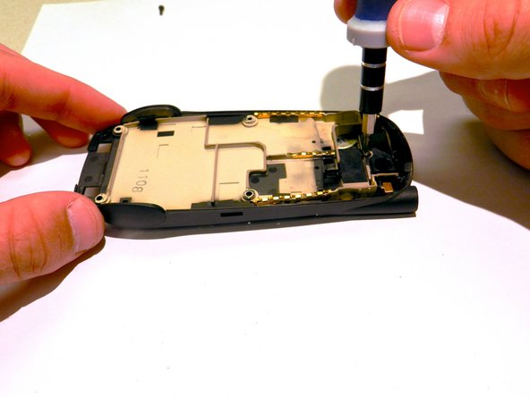 Image 3/3: Remove the 2 mm screw from the top of the inner back casing of the phone.