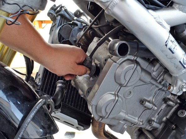 Remove the spark plug cap from cylinder 1 by grabbing the plug cap boot and pulling straight out.