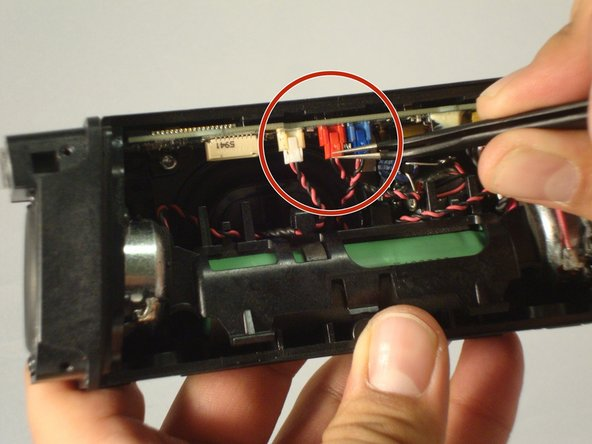 Undo the clips that are now exposed inside of the speaker. The colors of these clips are white, red, blue.