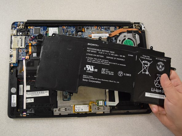 Lift the battery from the laptop to remove.