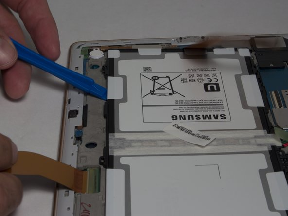 Move the plastic opening tool in a downward motion, away from the battery to bring the battery out of the device.