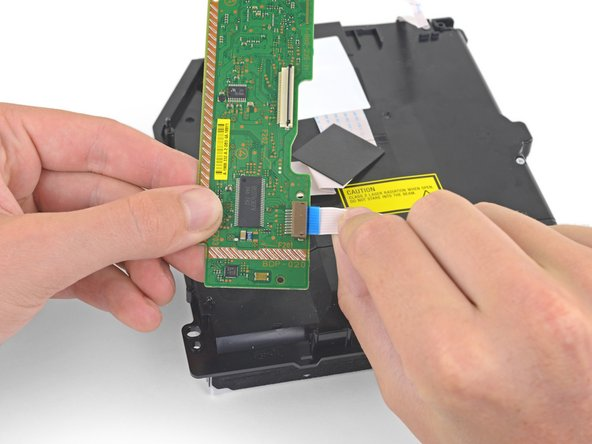 Hold the PCB in one hand and the lower ribbon cable in the other.