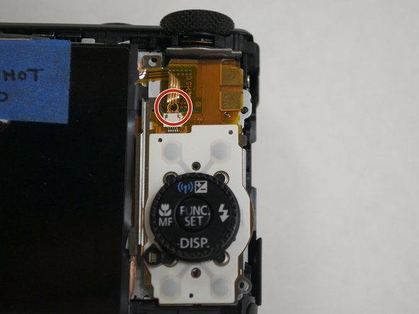 Using a plastic spudger, slowly pull out the ribbon using the hole shown in the image. The first of three logic connectors connecting the display to the camera is now removed.