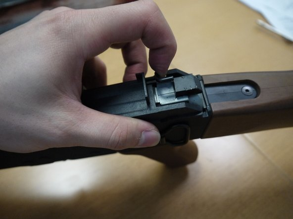 Pull the thin black rod away from the top cover button and swing it outwards.