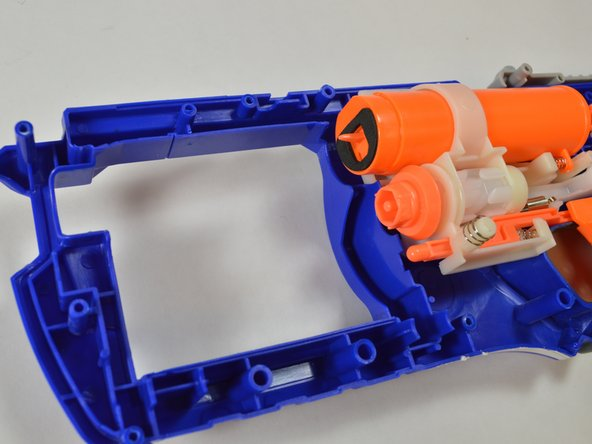 On the bottom half of the blaster, ensure the tab from the button makes contact with the barrel assembly.