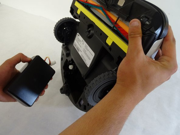 Remove the battery by holding the battery in place and partially righting the POWERbot so the battery falls out.