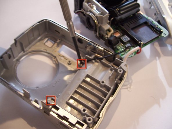 Use a Phillips screwdriver to unscrew the two screws that connect the inside battery casing to the front of the outer casing.