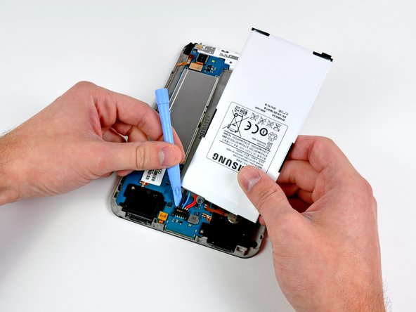 Image 1/1: Use the edge of a plastic opening tool to pry the battery connector straight up off its socket on the motherboard.