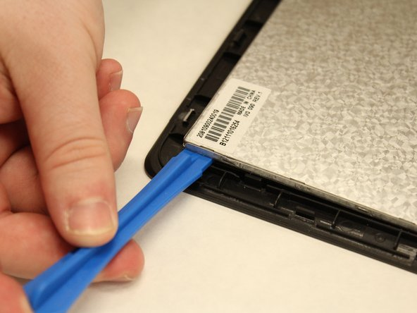 Place the plastic opening tool between the metal screen plate and the black front casing.