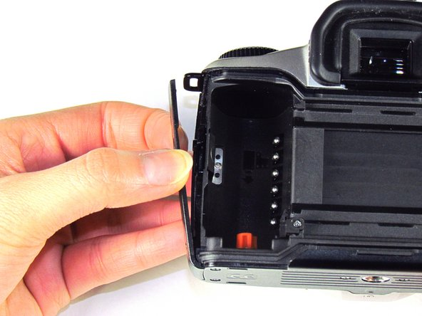Using your finger, carefully pry open the side panel from the top of camera.