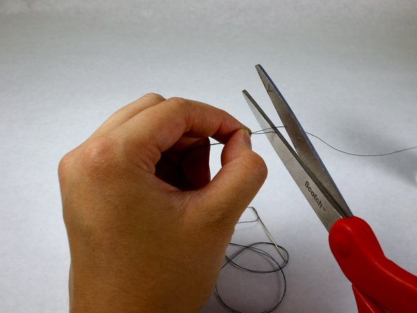 Match the length of the thread on each side of the loop and cut with the scissors.
