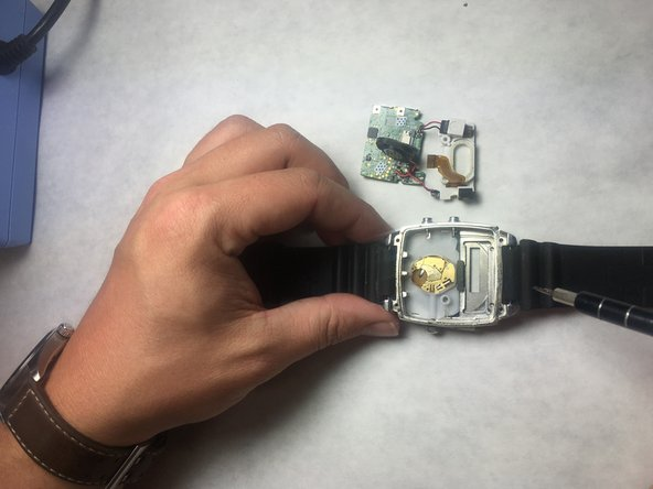 Grab the motherboard with tweezers and remove from watch cavity.