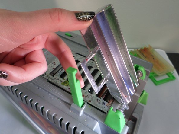 Image 1/3: Pop the metal arms out of the green pivot support.