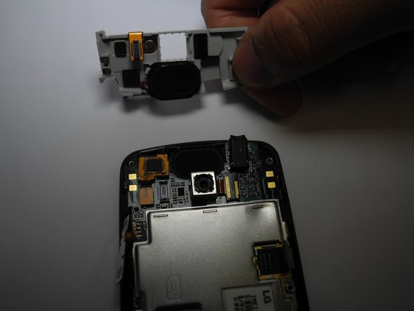 Remove SD card mount. Insert a plastic opening tool on the right side to pop off.