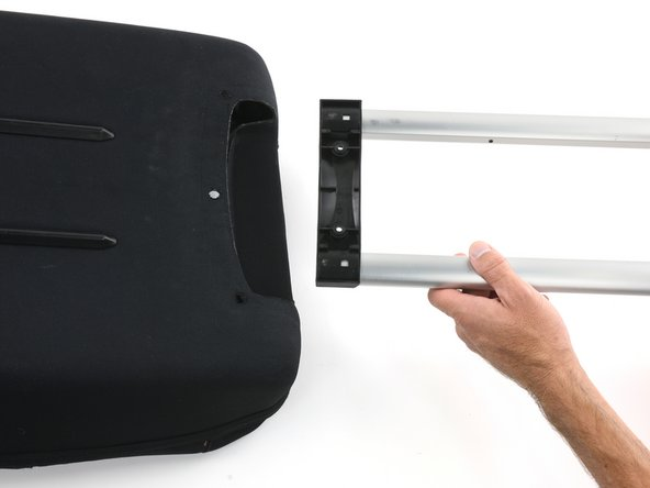 This step may take some force. It may help to push down on the back of the bag while pulling up on the outer edge of the plastic handle guard so the screw anchors can move up and out of the holes in the hard backing.