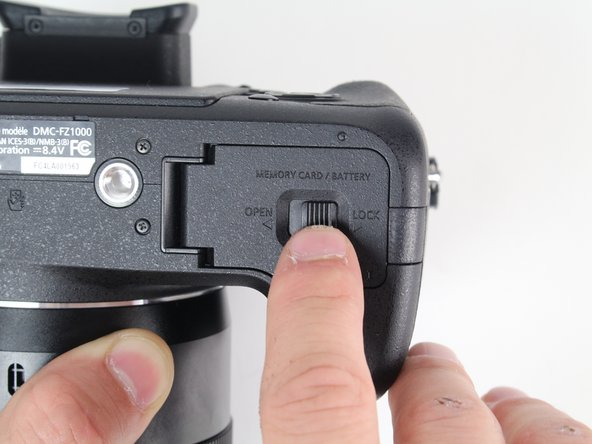 Slide the switch on the bottom of your camera from the right (LOCK) to the left (OPEN).
