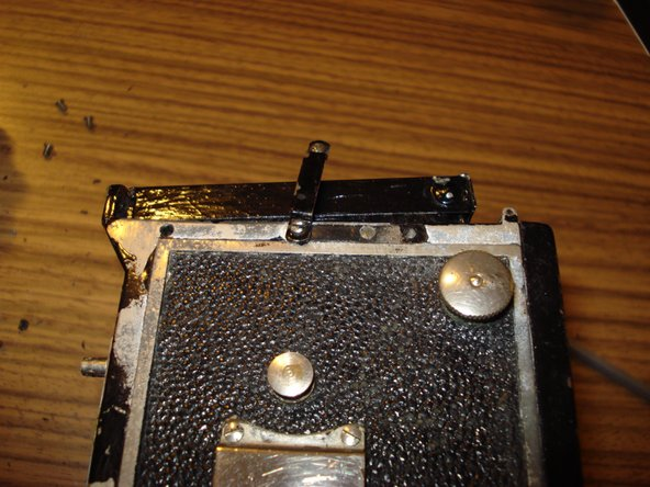Image 3/3: The finder is attached to the body with 6 screws. Two on the top behind the finder and two on each side. On both sides, one screw is at the front end of the camera and one is hidden behind the camera strap holder which thus has to be removed at least halfway.