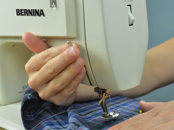 Image 2/3: Put the garment in the machine, starting a few inches before the torn seam to overlap with the stitches.