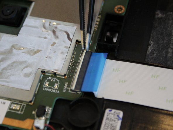 Using the blue tab, gently pull the ribbon away from the motherboard.
