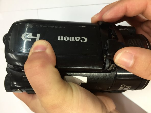 Using your fingers, remove the black plastic covering. Underneath the covering, you will find a screw hinge.