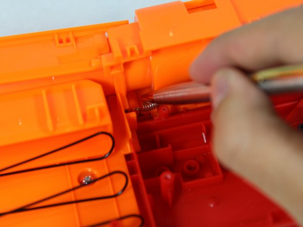 Using a small tool, carefully remove the spring from its pegs.