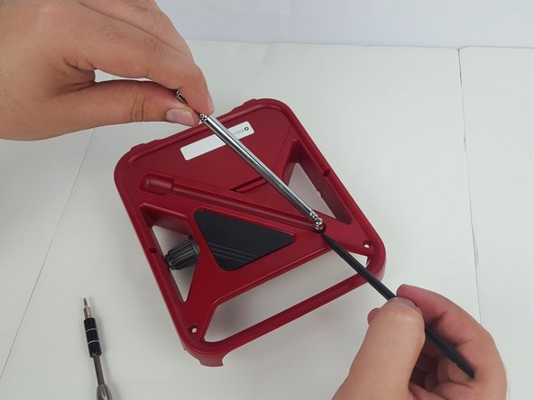 From the back of the device, gently pull the antenna out of the device case.