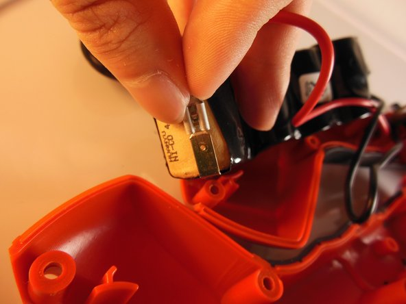 Unplug the battery by pulling out both the red and black wires. They should come out easily with a little bit of force.