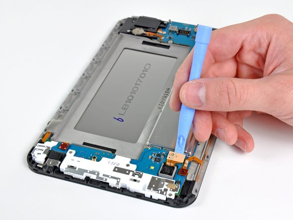 Image 1/3: The rear-facing camera connector is pried up from its socket on the motherboard with the edge of an opening tool.