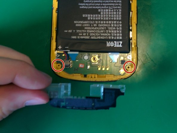 Remove the two black Philips head screws from the battery connector cover.