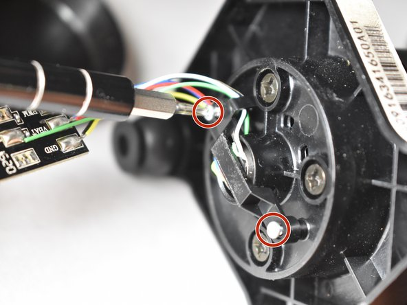 Using the Philips #000 screwdriver, unscrew the two 5.9 mm screws and remove the retaining clip on top of the motor piece.
