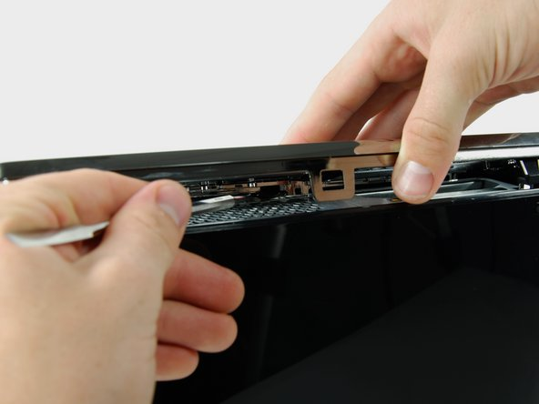 Image 1/2: Lift the left edge of the bottom bezel up enough to gain clearance.