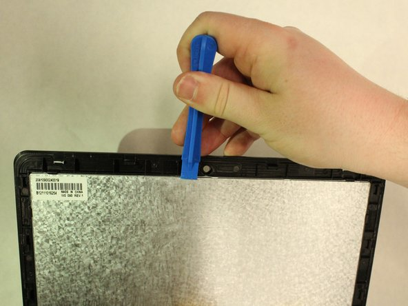 Continue to slide the opening tool along the length of the casing until there is a clear separation between the screen and the cover (as shown in the third image).