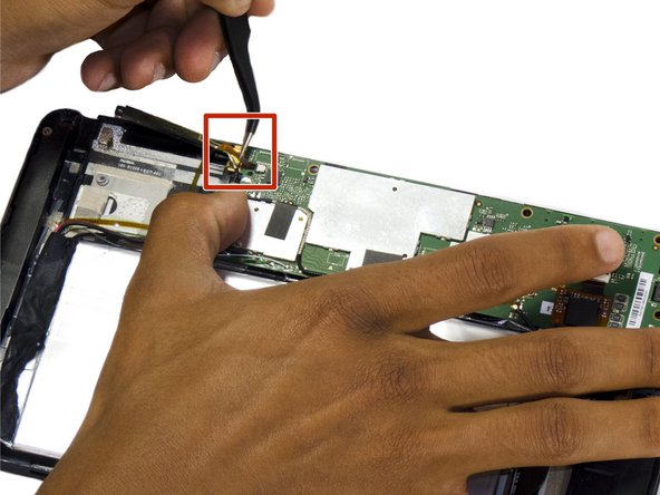 Carefully use the precision tweezers to unplug the ribbon cable.
