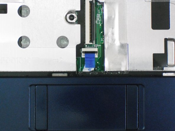 Image 1/3: Using the blue tab, pull the trackpad ribbon cable from its socket on the motherboard.