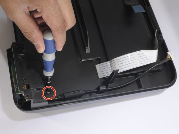Remove the only screw on the printer hood's underside, as shown. Use a T-9 screwdriver.