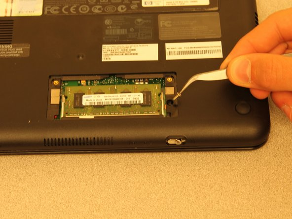 Remove the 4.9mm screw located to the right of the of the memory card using a PH1 screwdriver.