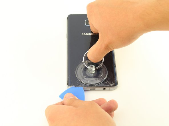 Once the device is very warm to the touch, place a suction cup near the bottom of the back of the device.