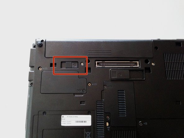 Image 1/3: Push release button to the left to release battery and gently pull battery from the laptop