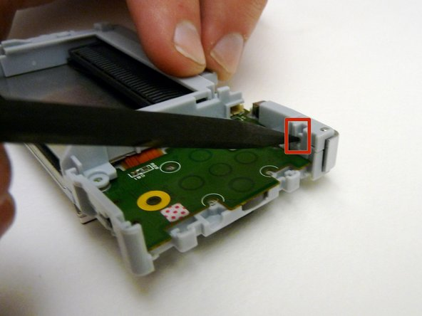 With a spudger, depress the small clip on the lower right corner of the plastic guard.