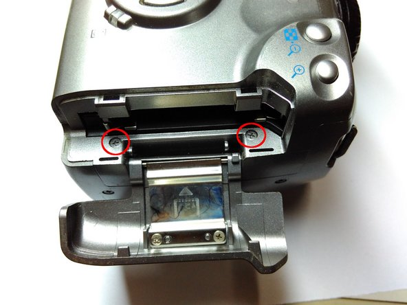 Open the CF card compartment by moving it upwards and tilting it away from the camera body.