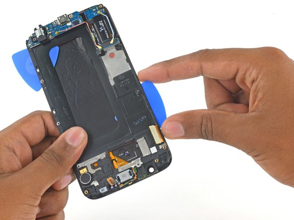 Image 3/3: Insert a second opening pick between the frame and display assembly on the display cable side of the phone.