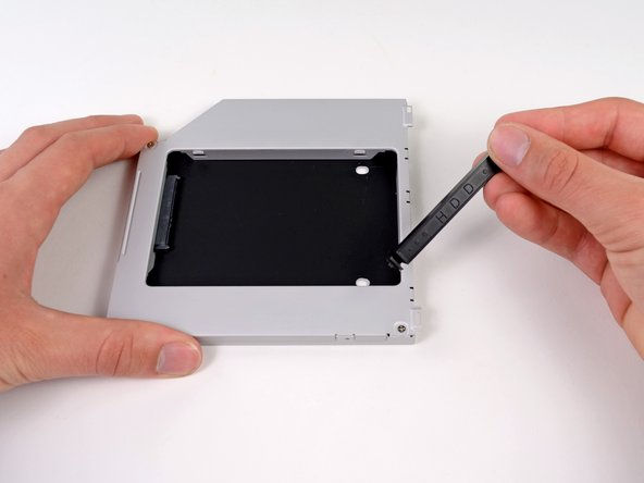 Image 2/2: Remove the plastic spacer from the optical bay hard drive enclosure by pressing in on one of the clips on either side and lifting it up and out of the enclosure.