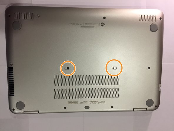 Flip the laptop over on its back and remove the two depressed stickers in the middle to reveal the two central 6.0mm Phillips-head  screws.