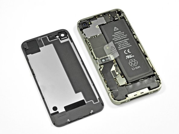 We continue to tread largely familiar waters as we remove the back cover, the same way we did with the iPhone 4, and reveal the battery along with a mess of padded EMI shields.