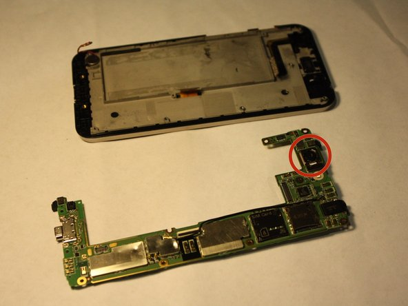 Image 1/2: Grasp the sides of the camera with the tweezers and carefully remove the camera from the logic board.