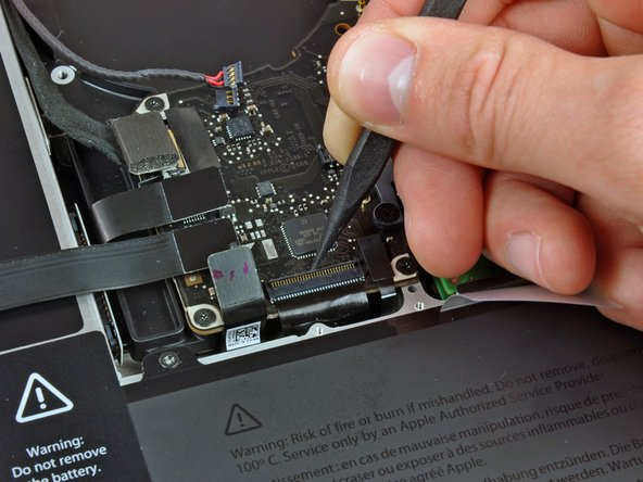 Image 2/3: Use your spudger to slide the keyboard ribbon cable out of its socket.