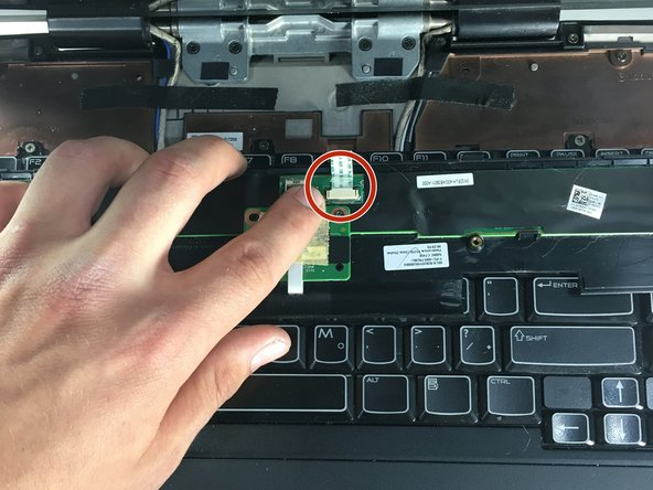 Position the laptop normally, with the bottom on the ground and the screen flipped up towards you. Use the same plastic opening tool to lift the power button panel. Once lifted, unclip the power button using tweezers on the two black clips. Remove the panel completely.