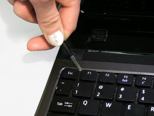 Starting in one corner, use tweezers to push the tabs inward to release the keyboard and then use the tweezers to gently pry the keyboard up and away from the laptop.