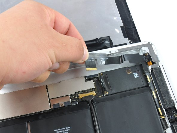 Run a plastic opening tool underneath the headphone jack and front-facing camera cable to free it from the adhesive attaching the cable to the rear panel.